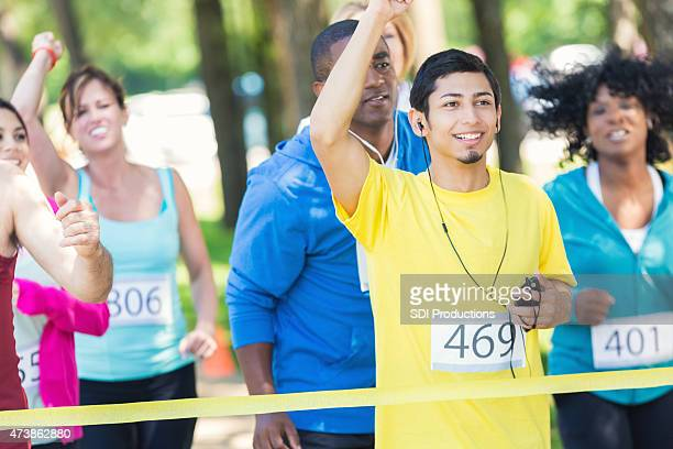 Young Hispanic man smiling as he wins marathon race