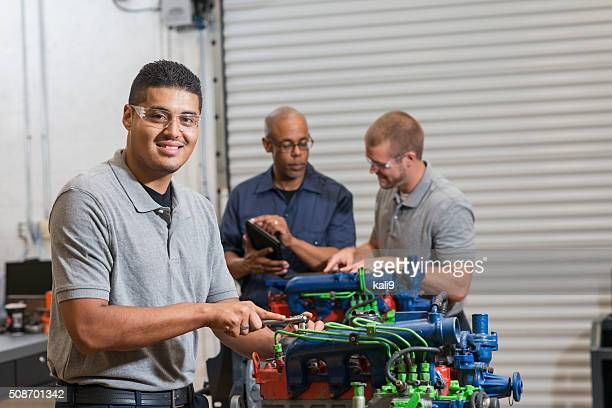 Young Hispanic man training to be auto mechanic