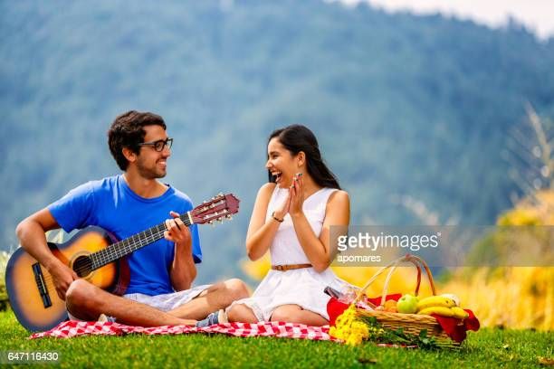 Young hispanic or latin couple enjoying picnic outdoors at meadow