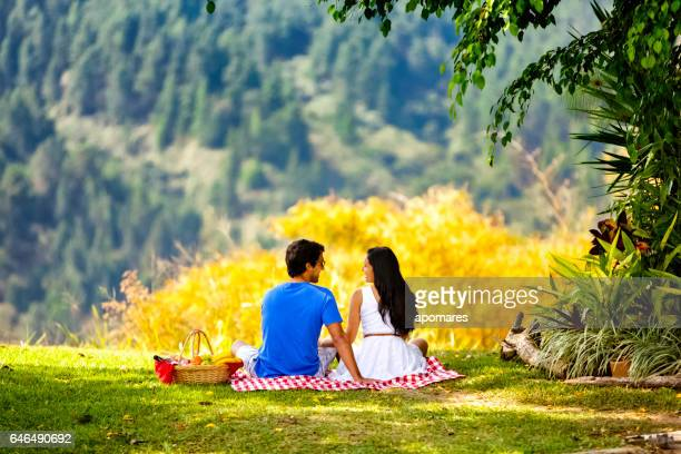 Young hispanic or latin couple enjoying picnic outdoors at park