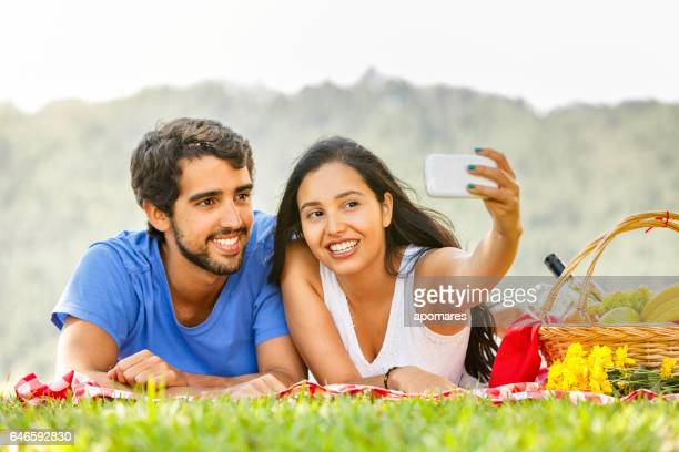Young hispanic or latin couple taking a selfie at meadow