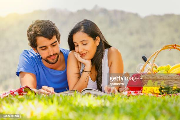 Young hispanic or latin happy couple reading book at park