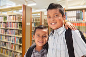 Happy Young Hispanic Student Brothers In Library.