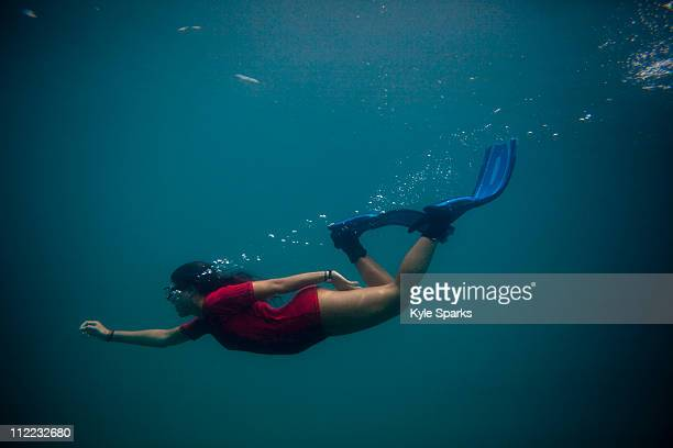 A young Hispanic woman free dives in the Caribbean Sea.