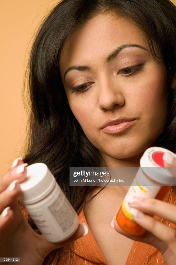 Young Hispanic woman looking at medication bottles