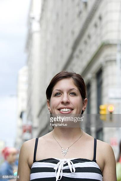 Young Hispanic woman looking upward in downtown city