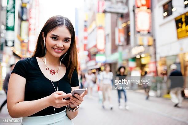 Young hispanic woman, smiling and looking at camera, shopping, Tokyo