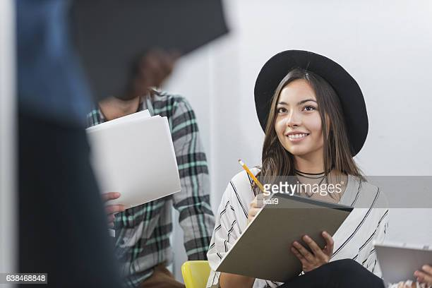 Young Hispanic woman taking notes in meeting