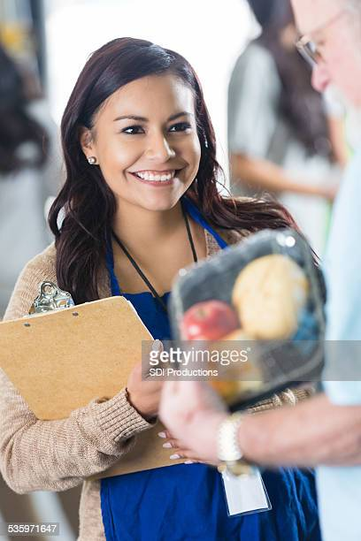Young Hispanic woman volunteering at soup kitchen or food bank
