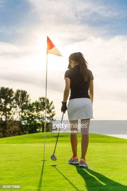 Jungen hispanischen Frauen Golf spielen