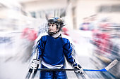 Kid hockey player in the hockey equipment and street in line skates