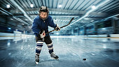 Young hockey player ready to make a strong shot against ice arena background