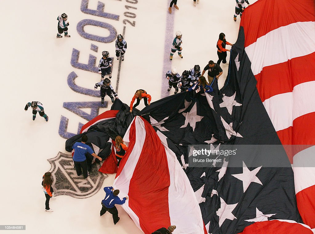 Young hockey players fall to the ice while practicing carrying the flag prior to the game between the Dallas Stars and the New York Islanders at the Nassau Coliseum on October 9, 2010 in Uniondale, New York.