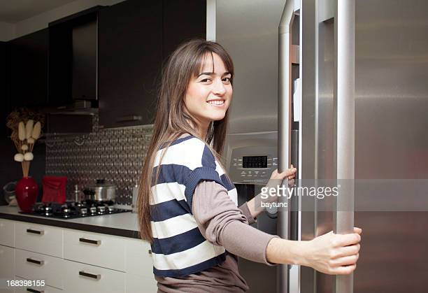 Young home maker checks the contents of her refrigerator,