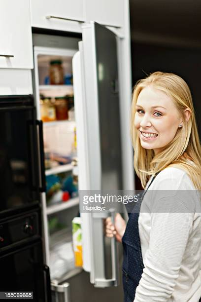 Young home maker checks the contents of her refrigerator, smiling