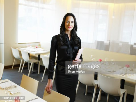 Young hostess holding menus in restaurant, portrait : Stock Photo