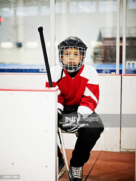 Young ice hockey player sitting on players bench