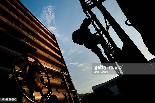 A young immigrant heading from El Salvador to the United States climbs up the cargo train called El Tren de la Muerte on a train station in Arriaga...