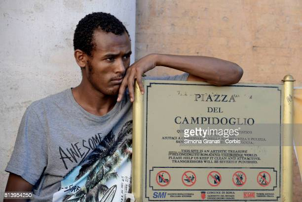 Young immigrant leaning on the Capitol plate on July 13 2017 in Rome Italy No one is illegal demonstration in Campidoglio against Virginia Raggi...