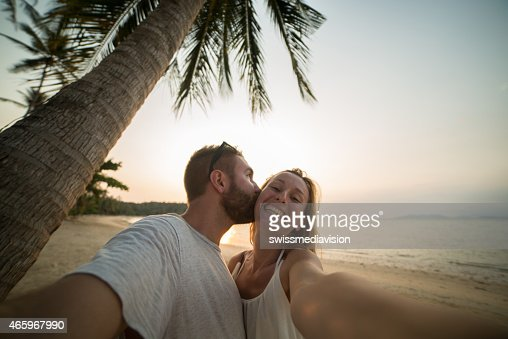 Young in love couple taking selfie while kissing