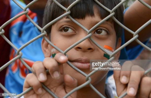 A young India fan watches India's Yuvraj Singh through a fence during the 2nd Test match between India and England at the Wankhede Stadium Mumbai...
