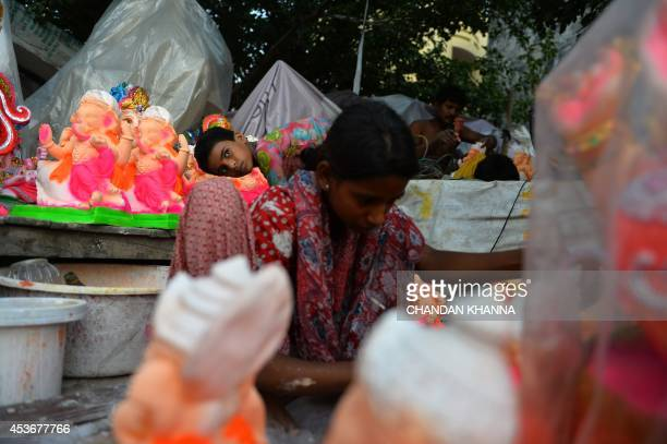 A young Indian artist looks as she paints a statue of a Hindu god ahead of The Janmashtami Festival which celebrates the birthday of Lord Krishna at...