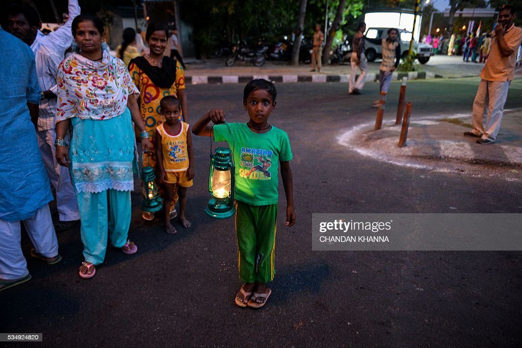 A Young Indian boy and a supporter of All India Congress Party carries caroline lantern as mark of protest during a rally against Delhi state government, Aam Admi Party and India's ruling government, Bhartiya Janta Party over water crises and power shortage in New Delhi on May 28, 2016. / AFP / CHANDAN