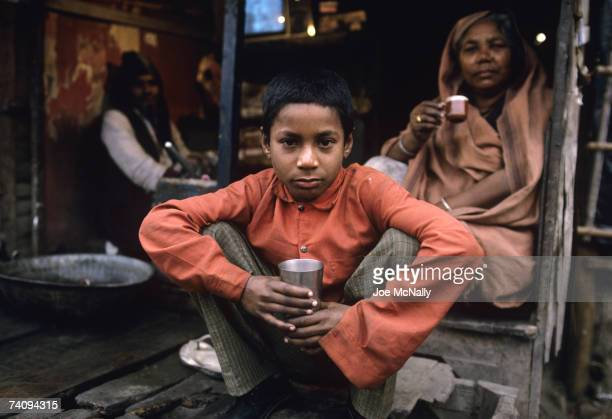 Young Indian boy enjoys tea with his family in January of 1999 in the slums of New Delhi in the Indus Valley region of India The Indus Valley...