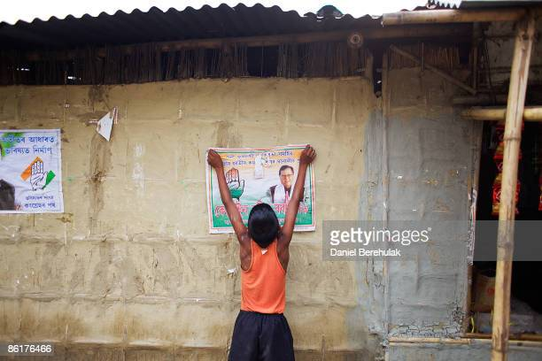 A young Indian boy hangs up a poster of a Congress Party candidate near a polling station on April 23 2009 in the Muslim dominated town of Mukalmua...