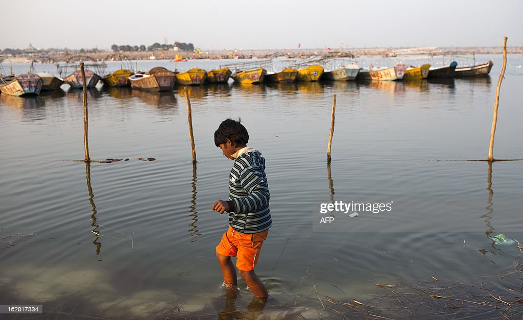 A young Indian boy looks for coins and other offerings at the Sangam or confluence of the Yamuna, Ganges and mythical Saraswati rivers at the Kumbh Mela in Allahabad on February 18, 2013. The Kumbh Mela in the town of Allahabad will see up to 100 million worshippers gather over 55 days to take a ritual bath in the holy waters, believed to cleanse sins and bestow blessings. AFP PHOTO/ Andrew Caballero-Reynolds