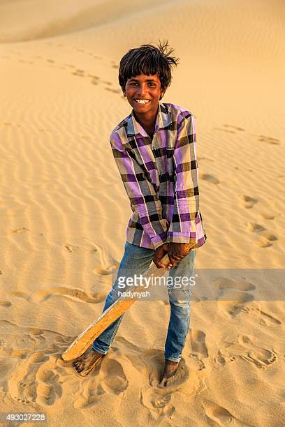 Young Indian boy playing cricket on sand dunes, India