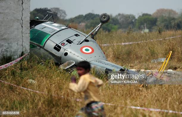 TOPSHOT A young Indian boy runs past the wreckage of a Chetak helicopter that crashed while attempting to land in a village near Bamrauli Air Base in...