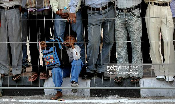 A young Indian boy watches as runners take part in the 2012 Airtel Delhi halfmarathon in New Delhi on September 30 2012 Edwin Kipyego of Kenya...