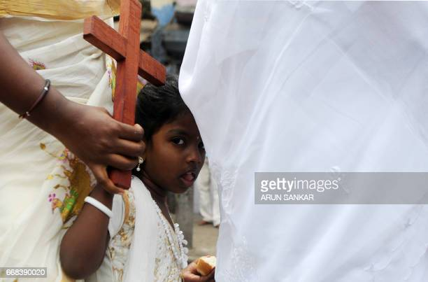 A young Indian Catholic child holds a cross as she takes part with others in a procession to reenact the crucifixion of Jesus Christ on the occasion...