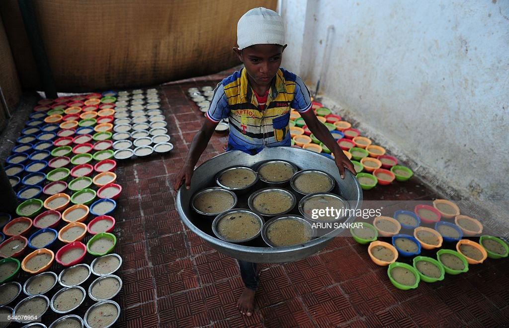 A young Indian child carries bowls of porridge(Nombu kanji)for the Iftar meal during the Islamic month of Ramadan at The Wallajah Big Mosque in Chennai on July 1, 2016. Across the Muslim world, the faithful fast from dawn to dusk and abstain from eating, drinking, smoking and having sex during that time as they strive to be more pious and charitable. / AFP / ARUN