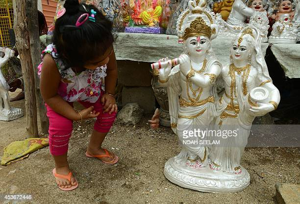 A young Indian child looks at a statue of the Hindu God Lord Krishna and his wife Radha at a roadside stall in Hyderabad on August 16 ahead of The...