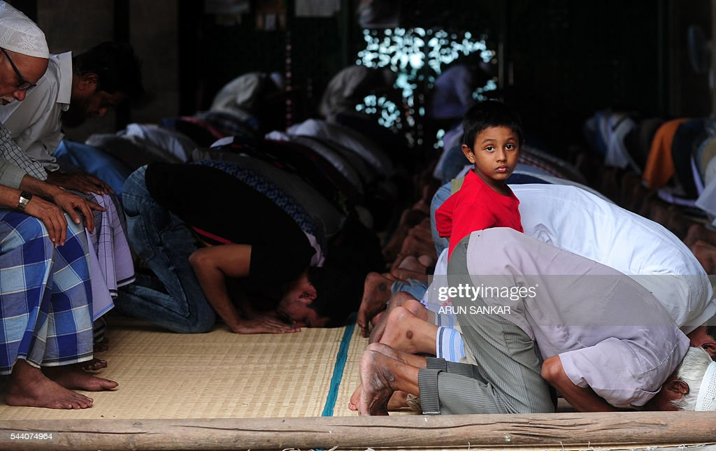A young Indian child looks on as Muslims take part in Friday prayers at The Wallajha Big Mosque during the Islamic month of Ramadan in Chennai on July 1, 2016. Across the Muslim world, the faithful fast from dawn to dusk and abstain from eating, drinking, smoking and having sex during that time as they strive to be more pious and charitable. / AFP / ARUN