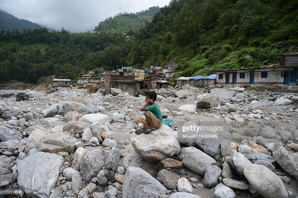 A young Indian child sits on boulders in Sonprayag on July 2, 2013, in a flood affected area of the northern Indian state of Uttrakhand. Construction along river banks will be banned in a devastated north Indian state amid concerns unchecked development fuelled last month's flash floods and landslides that killed thousands, the state's top official said. The Chief Minister of Uttarakhand, Vijay Bahuguna, also announced that a regulatory body would be set up to scrutinise future construction as the Himalayan state begins the herculean task of rebuilding following the June 15 floods.