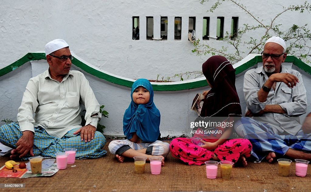 A young Indian child sits with Muslims as they prepare to break the fast with the Iftar meal during the Islamic month of Ramadan at The Wallajah Big Mosque in Chennai on July 1, 2016. Across the Muslim world, the faithful fast from dawn to dusk and abstain from eating, drinking, smoking and having sex during that time as they strive to be more pious and charitable. / AFP / ARUN