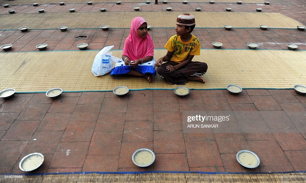 Young Indian children sit with bowls of porridge(Nombu kanji)as they prepare to break the fast with the Iftar meal during the Islamic month of Ramadan at The Wallajah Big Mosque in Chennai on July 1, 2016. Across the Muslim world, the faithful fast from dawn to dusk and abstain from eating, drinking, smoking and having sex during that time as they strive to be more pious and charitable. / AFP / ARUN