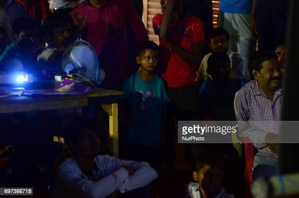 A young indian cricket fan as others watches India vs Pakistan final cricket match of Champions trophy on a big projector screen in Allahabad on June...