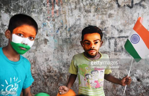 A young Indian cricket fan wears a mask of the face of India's captain Virat Kohli in Kolkata on June 18 to mark the Champions Trophy final between...