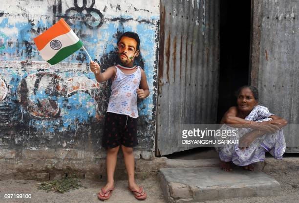 TOPSHOT A young Indian cricket fan wears a mask of the face of India's captain Virat Kohli in Kolkata on June 18 to mark the Champions Trophy final...