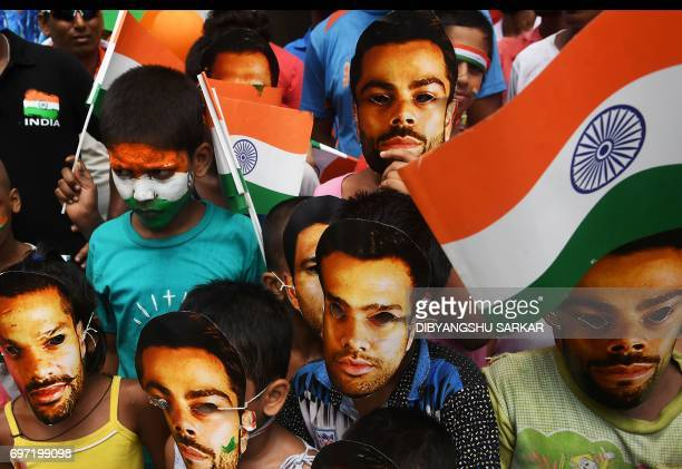 Young Indian cricket fans wear masks of the face of India's captain Virat Kohli and others in Kolkata on June 18 to mark the Champions Trophy final...