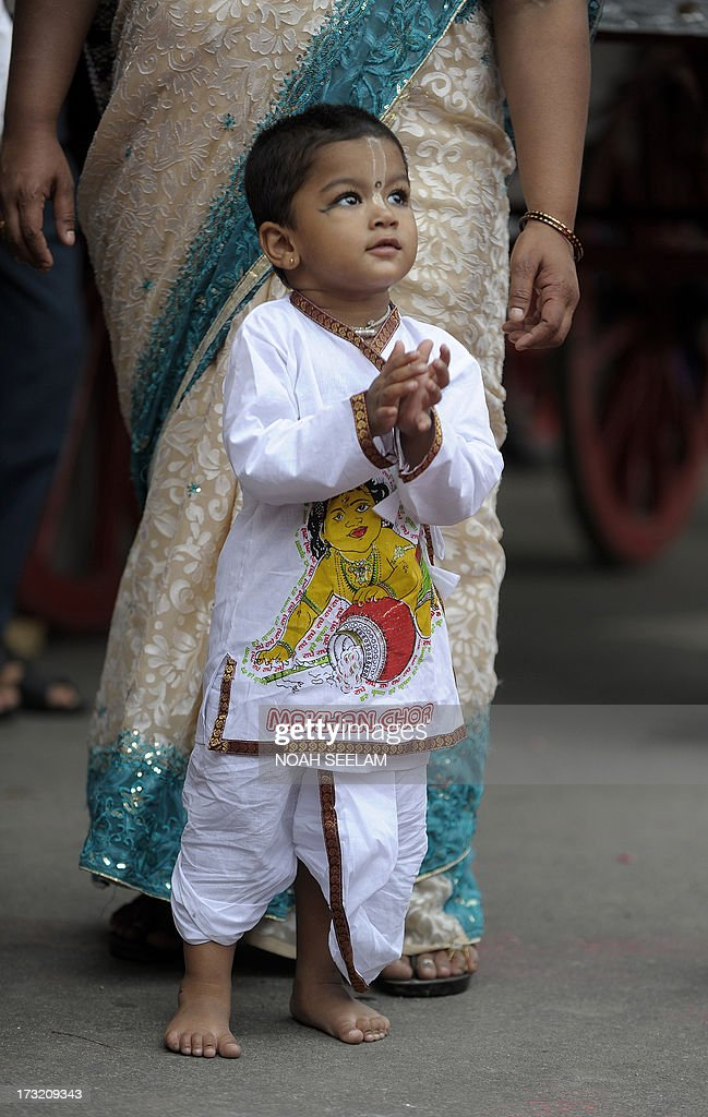 A young Indian devotee of The International Society of Krishna Conciousness (ISKON) watches at the start of the Sri Jagannatha Ratha Yatra in Hyderabad on July 10, 2013. According to mythology, the Ratha Yatra dates back some 5,000 years when Hindu god Krishna, along with his older brother Balaram and sister Subhadra, were pulled on a chariot from Kurukshetra to Vrindavana by Krishna's devotees. AFP PHOTO / Noah SEELAM