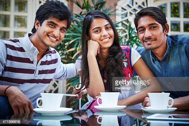 Young Indian Friends Smiling and Drinking Coffee at table