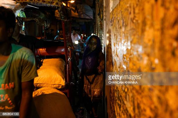 A young Indian girl makes her way down a crowded ally in the old quarters of New Delhi on May 9 2017 / AFP PHOTO / CHANDAN KHANNA