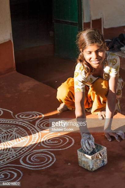 Young Indian girl painting with chalk on the ground