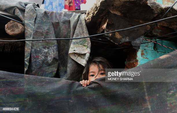 A young Indian girl peeps out from her shanty in a slum in New Delhi on March 18 2015 AFP PHOTO / MONEY SHARMA