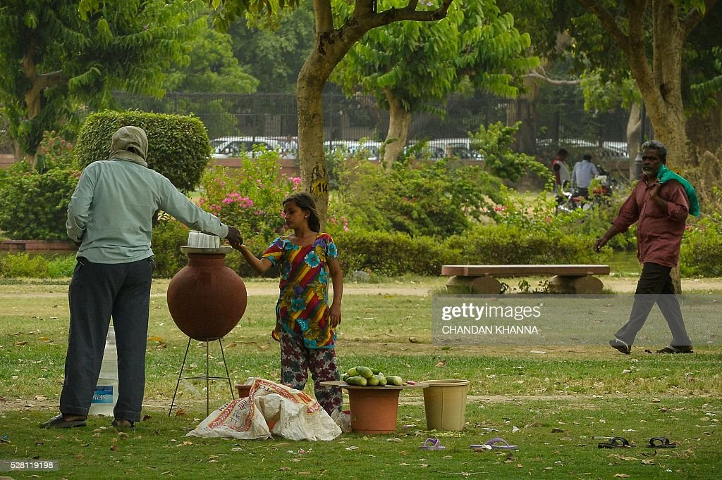 A young Indian girl receives money from a customer as she sell water and fruit in New Delhi on May 4, 2016. / AFP / CHANDAN